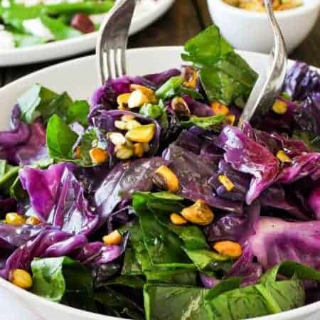 Warm Red Cabbage Salad with Garlic Herb Butter being tossed in a salad bowl.