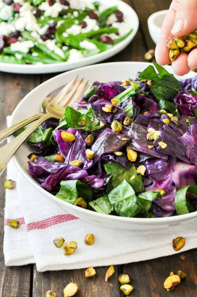 Sprinkling pistachio nuts on a Warm Red Cabbage Salad with Garlic Herb Butter in a white bowl.