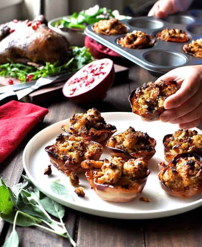 Hand reaching to take a Pork Sausage Apple Stuffing in Pancetta Cups (Muffin Tin) off a white plate.