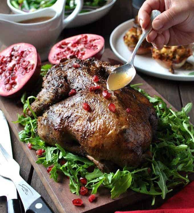 Festive Christmas Roast Duck sitting on a bed of rocket salad garnished with pomegranate seeds on a wooden board, ready for carving.