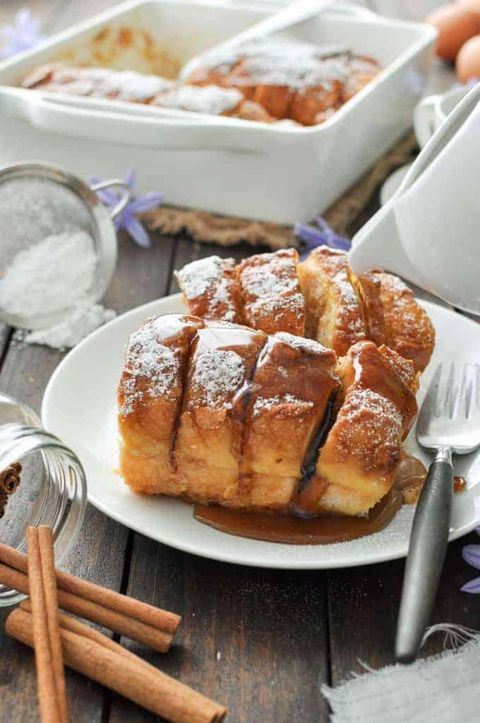 Hasselback Baked French Toast on a white plate, dusted with icing sugar and drizzled with maple syrup.