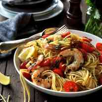 A bowl of Prawn Pasta with cherry tomatoes and lemon