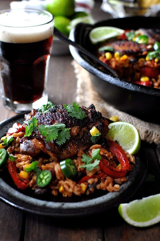 One Pot Mexican Chicken Rice on a dark brown plate with lime wedges on the side, ready to be eaten.