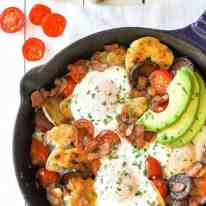 Chorizo Breakfast Hash with crispy smashed potatoes and eggs in a cast iron skillet with avocado on the side.