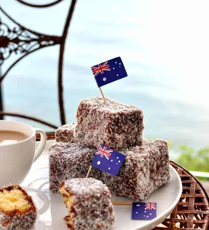 Lamingtons on a white plate outside with Australian flags