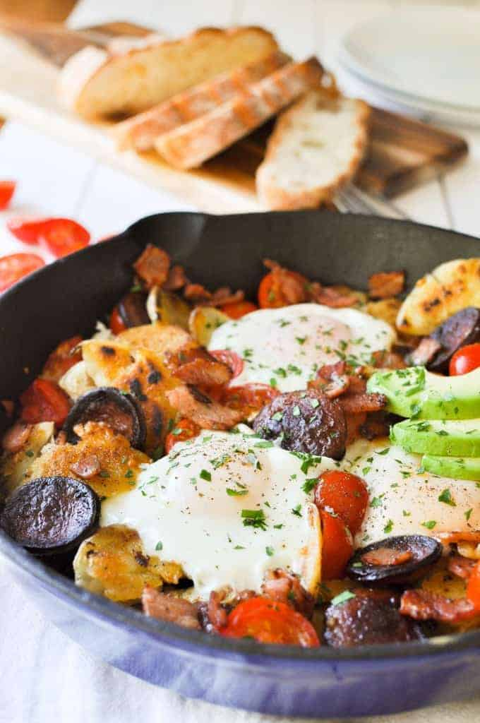Chorizo Breakfast Hash with crispy smashed potatoes and eggs in a cast iron skillet with avocado on the side with bread in the background.