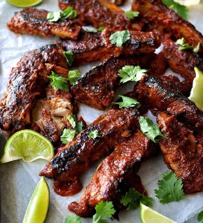 A tray of Oven Baked Ribs with Chipotle Barbecue Sauce scattered with cilantro