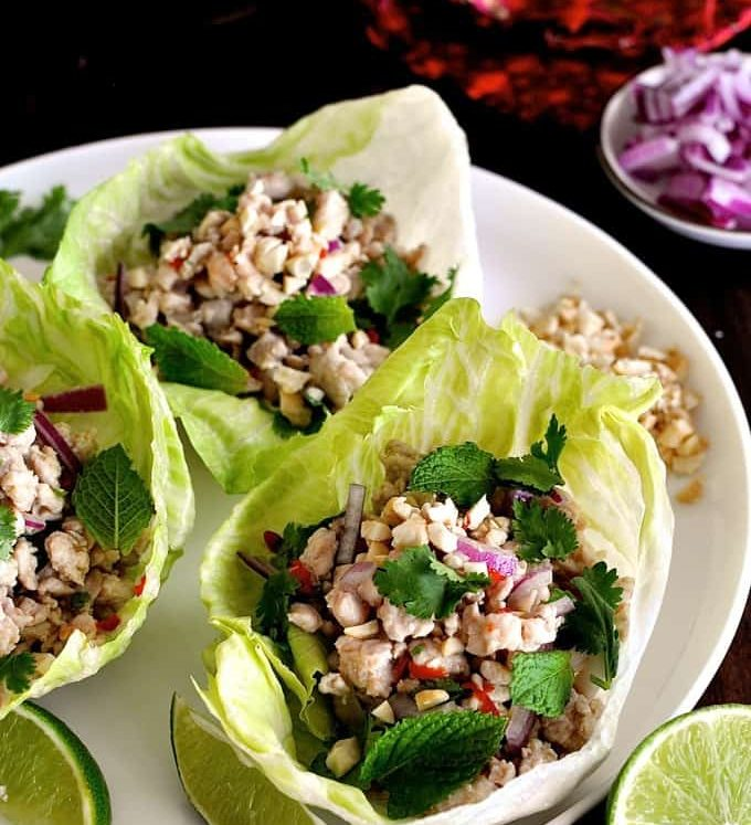 Thai Chicken Lettuce Wraps on a white plate with garnishes