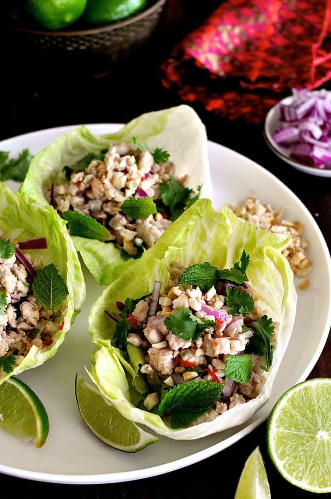Thai Chicken Lettuce Wraps on a while plate with garnishes