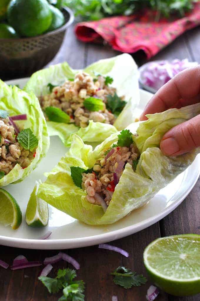 Hand grabbing a Thai Chicken Lettuce Wrap from a plate