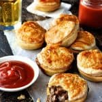 A stack of Party Pies on baking paper with tomato sauce (ketchup)
