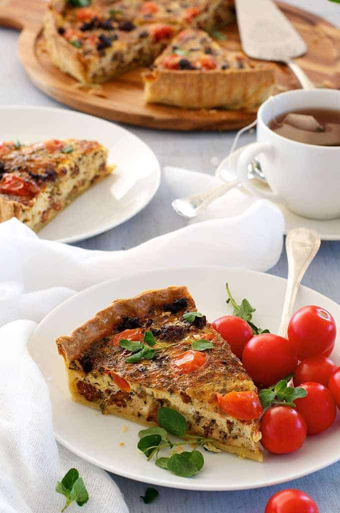 A slice of Italian Sausage Quiche with cherry tomatoes on the side