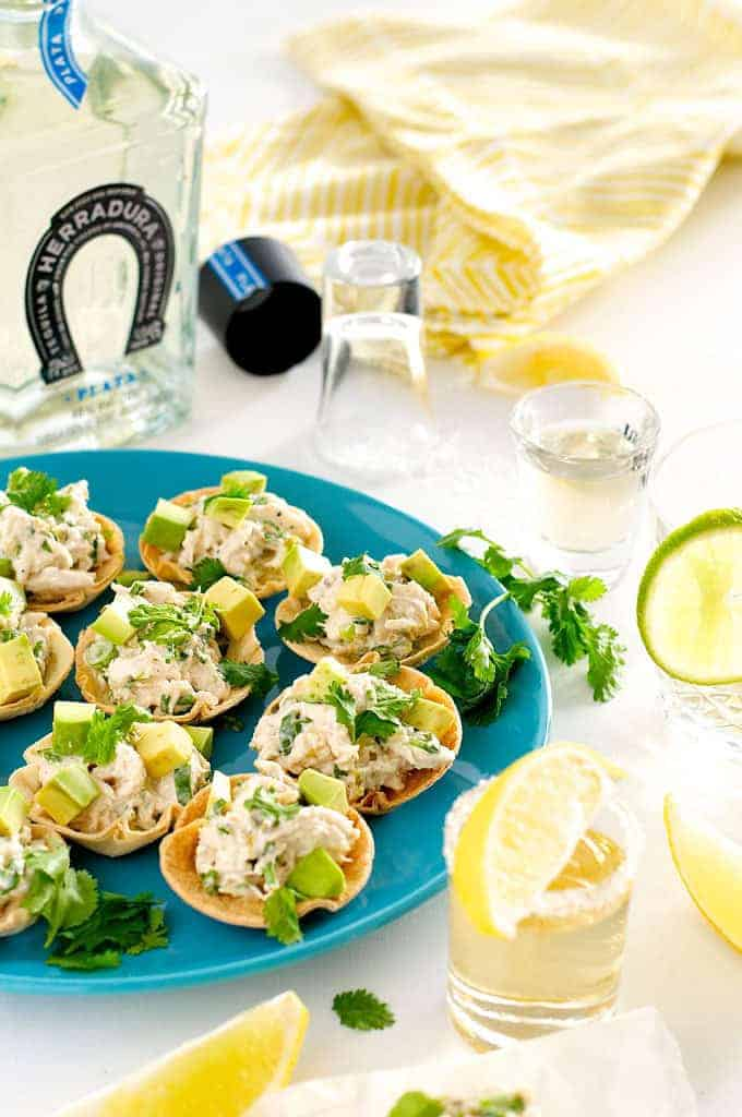 Table setting photo of Spicy Little Muffin Tin Chicken Tostadas with tequila bottle and glass