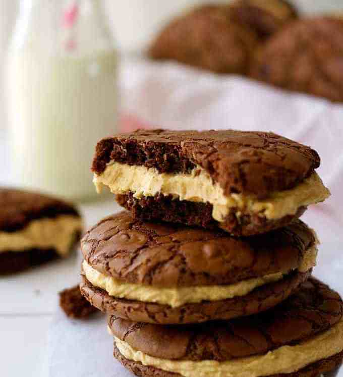 A pile of Brownie Cookie Sandwiches with Peanut butter Frosting, with milk in background