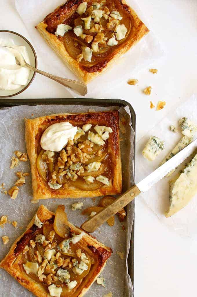 Caramelized Pear and Blue Cheese Tarts on a tray with a block of gorgonzola cheese