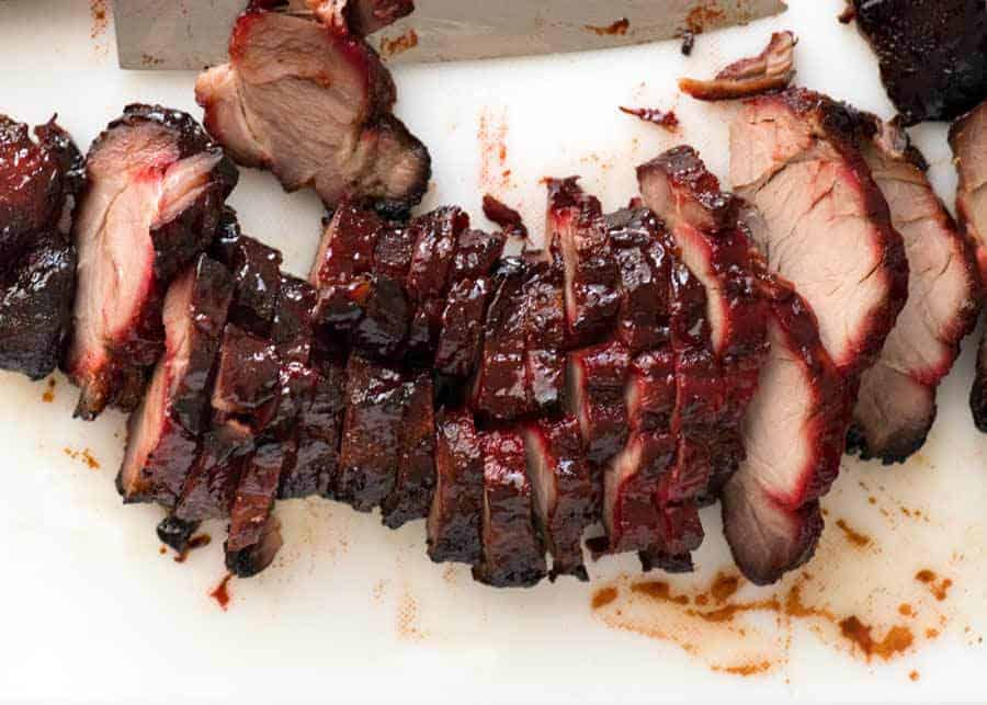 Overhead photo of Char Siu (Chinese Barbecue Pork) sliced on a white cutting board.