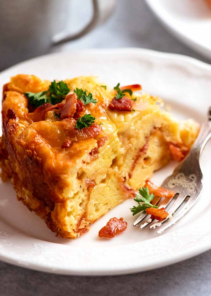 Slice of Cheese and Bacon Strata Cake - Breakfast Casserole, being eaten for breakfast