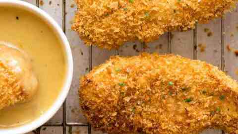 Crunchy Baked Chicken Tenders on a tray with a Honey Mustard Dipping Sauce on the side, fresh out of the oven