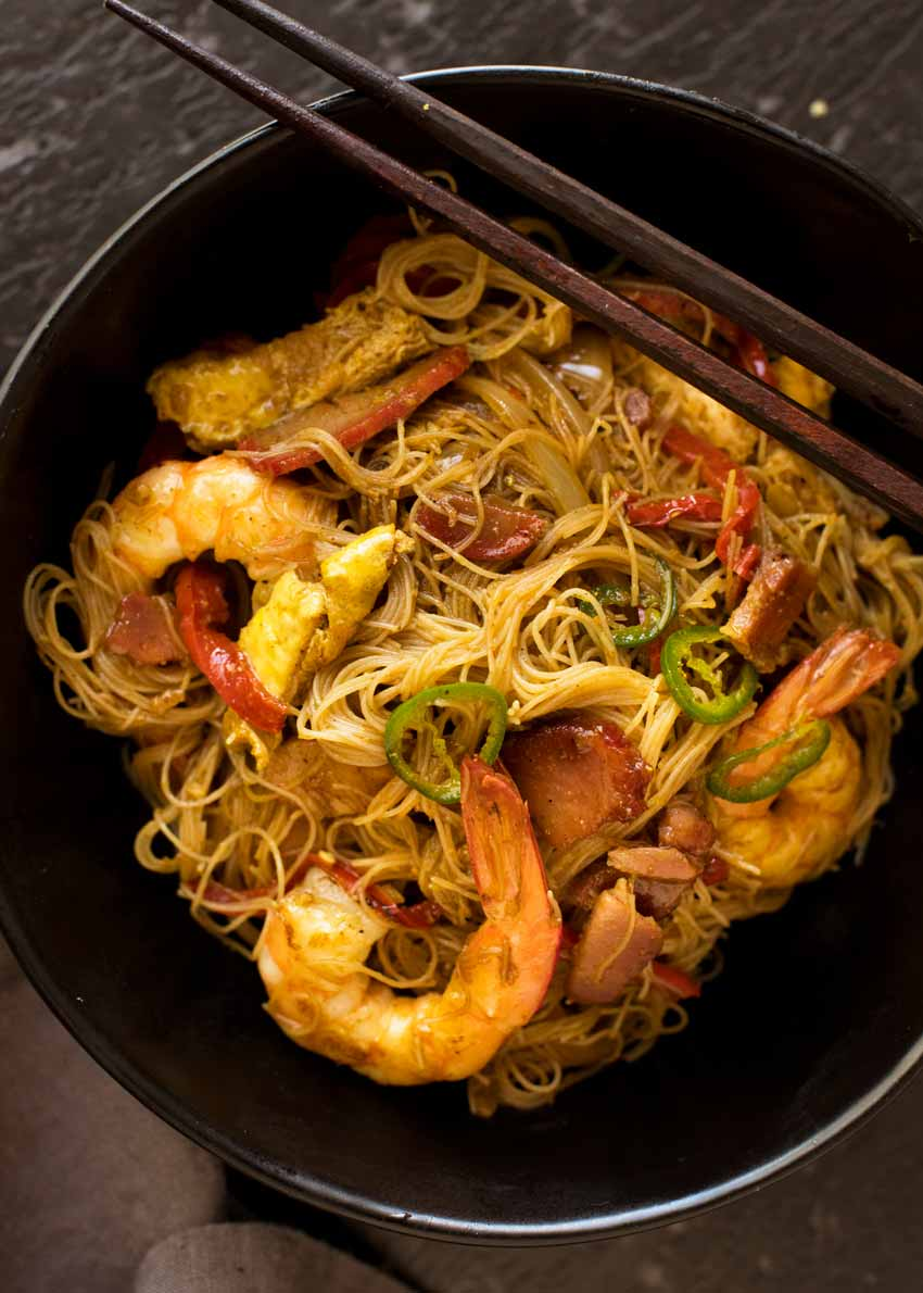 Overhead photo of Singapore Noodles in a black bowl with chopsticks resting on the edge, ready to be eaten.