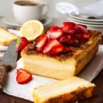 Cream Cheese Stuffed French Toast Loaf topped with strawberries, sliced on a board