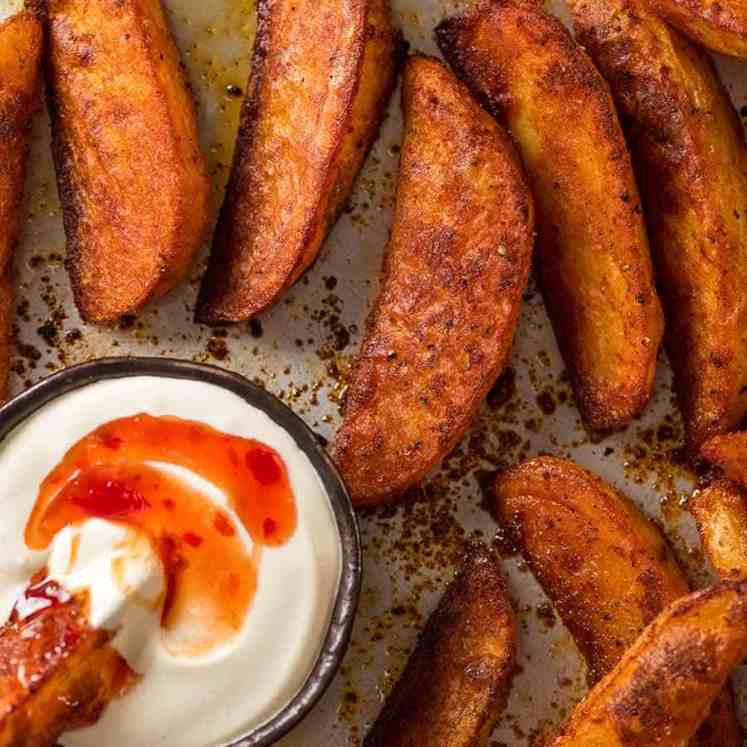 Overhead photo of crunchy baked potato wedges, fresh out of the oven