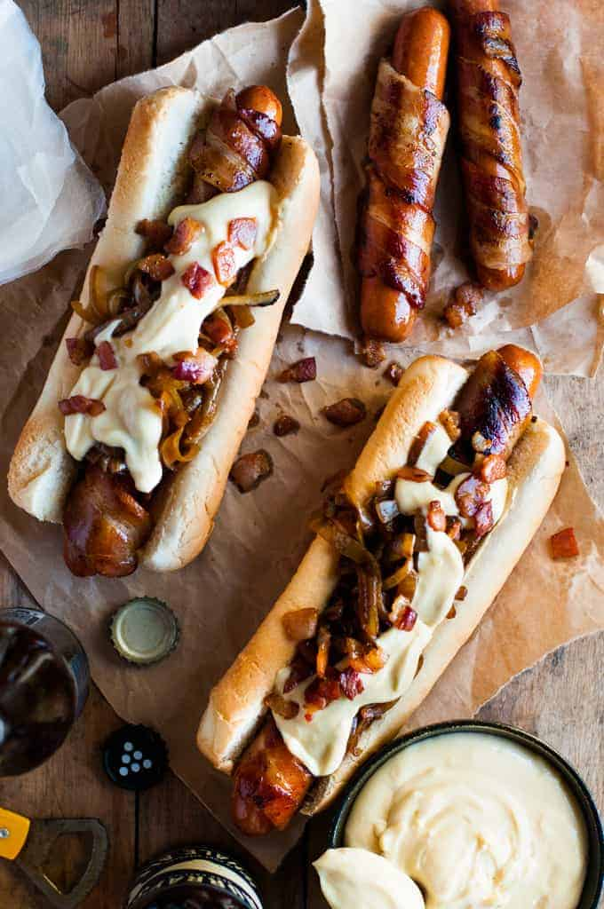 Bacon Wrapped Hot Dogs with Cheese Sauce with a pot of cheese sauce