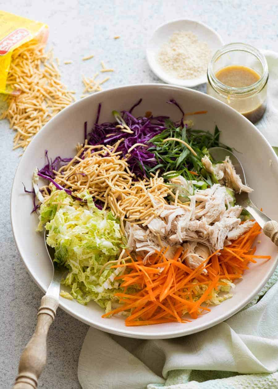 Chinese Chicken Salad with Asian Dressing in a white bowl, ready to be tossed