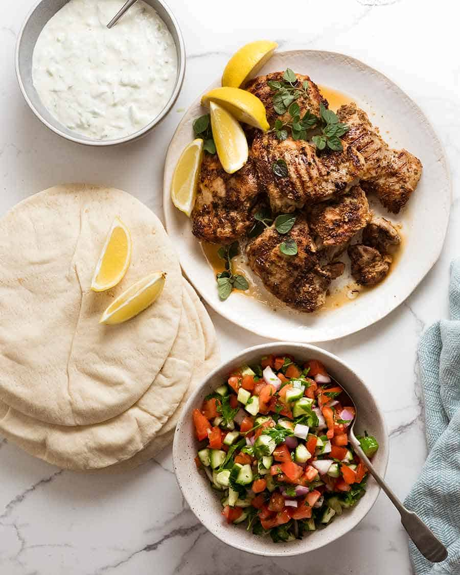 Photo of the components of Greek Chicken Gryos - marinated Greek Chicken, tzatziki and tomato cucumber salad.
