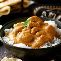 Butter Chicken on rice in a rustic black bowl, ready to be eaten