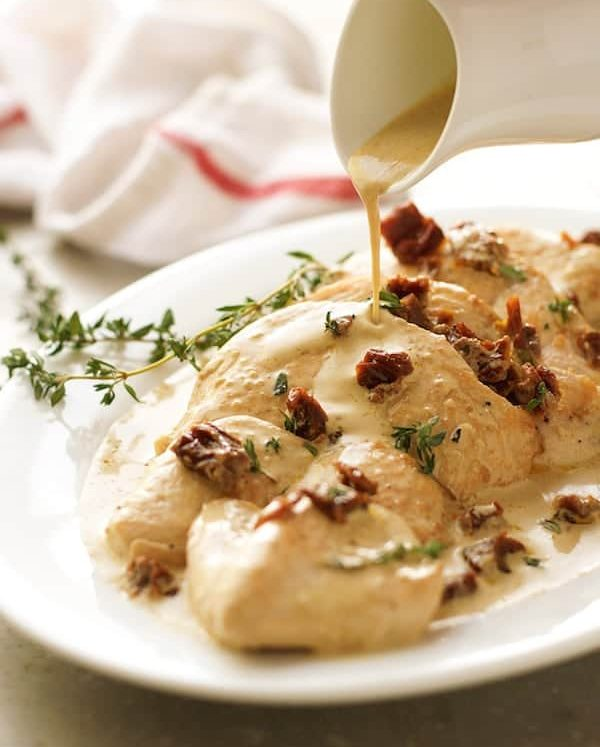 Pouring sauce over Chicken with Creamy Sun Dried Tomato Sauce