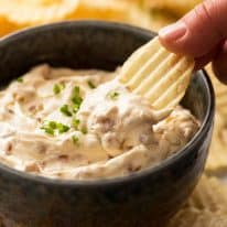 Hand dipping crinkle cut potato chips in creamy homemade French Onion Dip