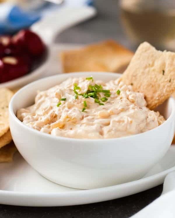 Homemade French Onion Dip in a white bowl with crispbread