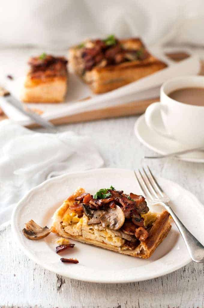 Slice of Bacon, Egg and Mushroom Tart on a white plate, ready to be eaten.