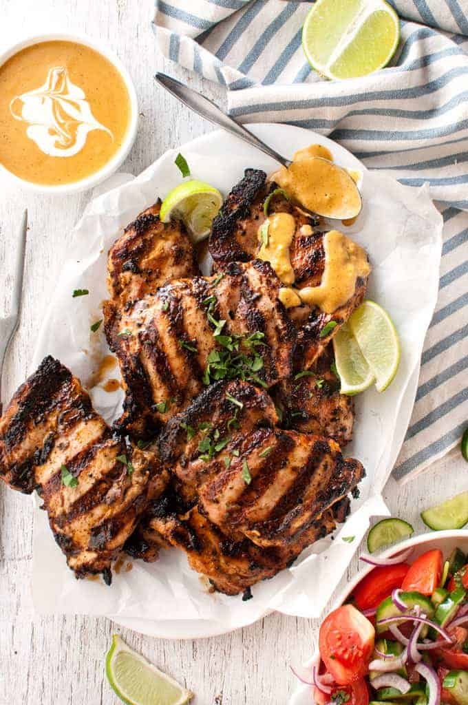 Grilled Coconut Marinated Chicken on a plate, drizzled with coconut sauce.
