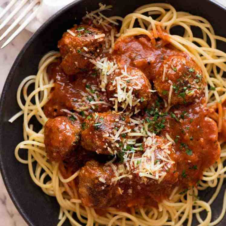 Overhead photo of Italian Meatballs in a rustic black bowl garnished with parmesan, ready to be eaten