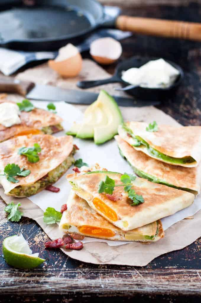 Sliced Egg, Bacon and Avocado Quesadillas with cilantro garnish