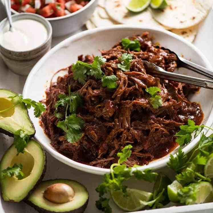 Mexican Shredded Beef taco spread - tortillas, sour cream, avocado, lime, pico de Gallo