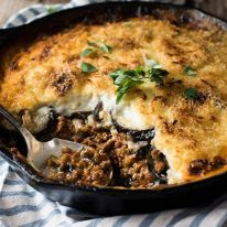 Moussaka in a black skillet, fresh out of the oven, ready to be served