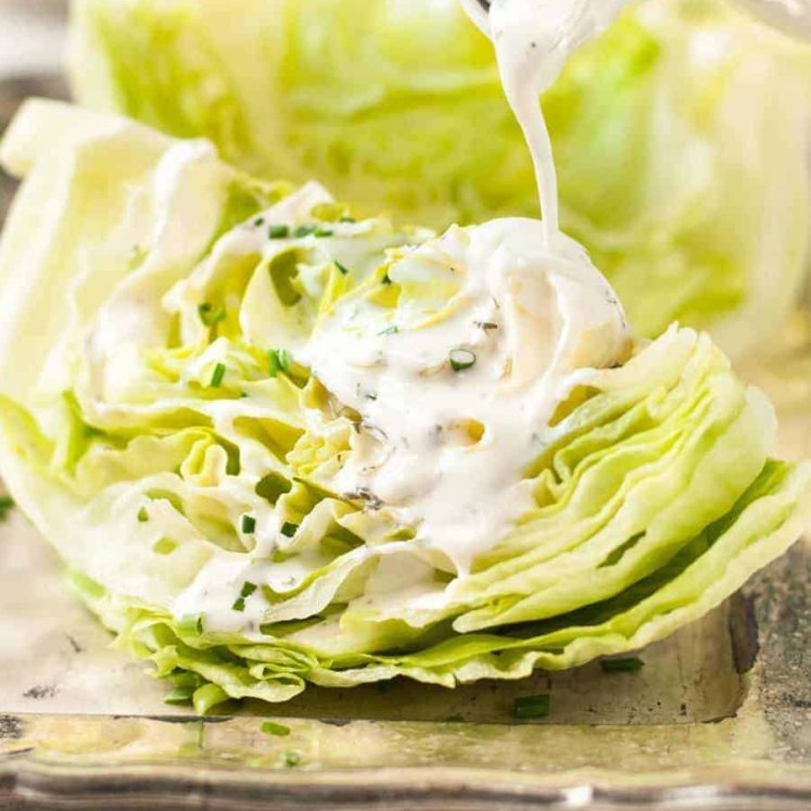 Pouring Ranch Dressing on lettuce wedges for Lettuce Wedge Salad