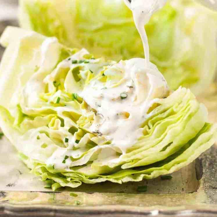 Pouring Ranch Dressing on lettuce wedges for Lettuce Wedge Salad