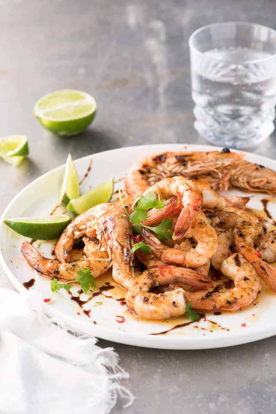 Asian Grilled Shrimp / Prawns on a white plate, drizzled with brown butter, lime and sweet soy, ready to be served.
