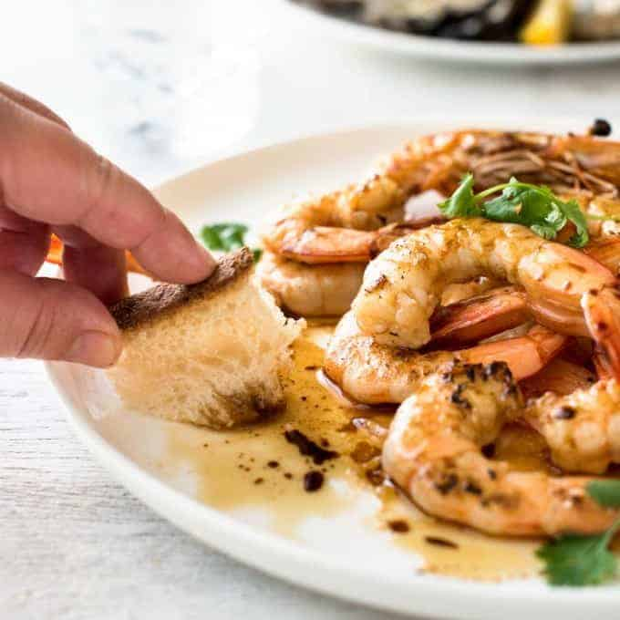 Bread being used to mop up the sauce on a plate of Asian Grilled Shrimp.