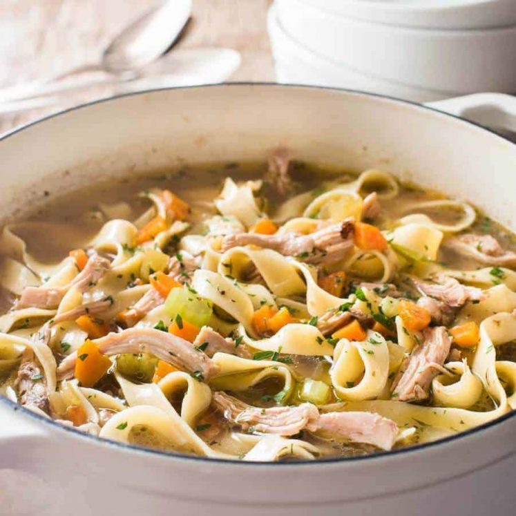 An easy Chicken Noodle Soup in a white cast iron pot, piping hot fresh off the stove.