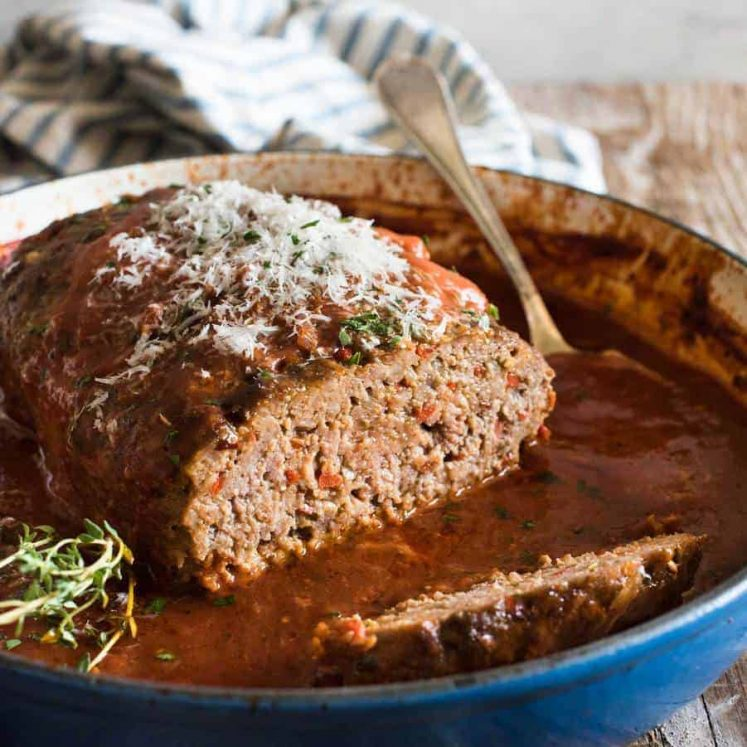Italian Meatloaf with tomato marinara sauce in a round blue casserole pan with the end sliced off, revealing the juicy inside.