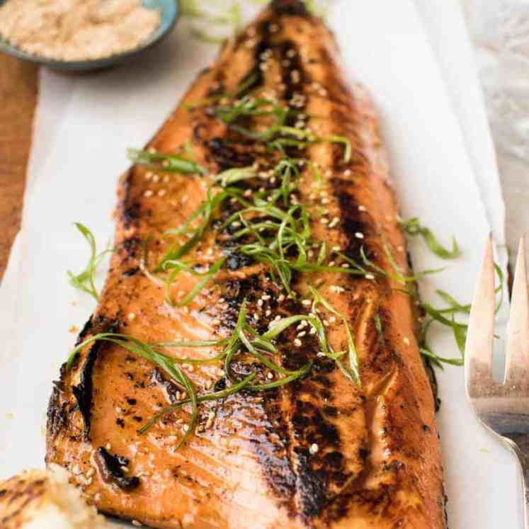 Japanese Miso Salmon Side on a wooden board garnished with steps of shallots / scallions, ready to be served.