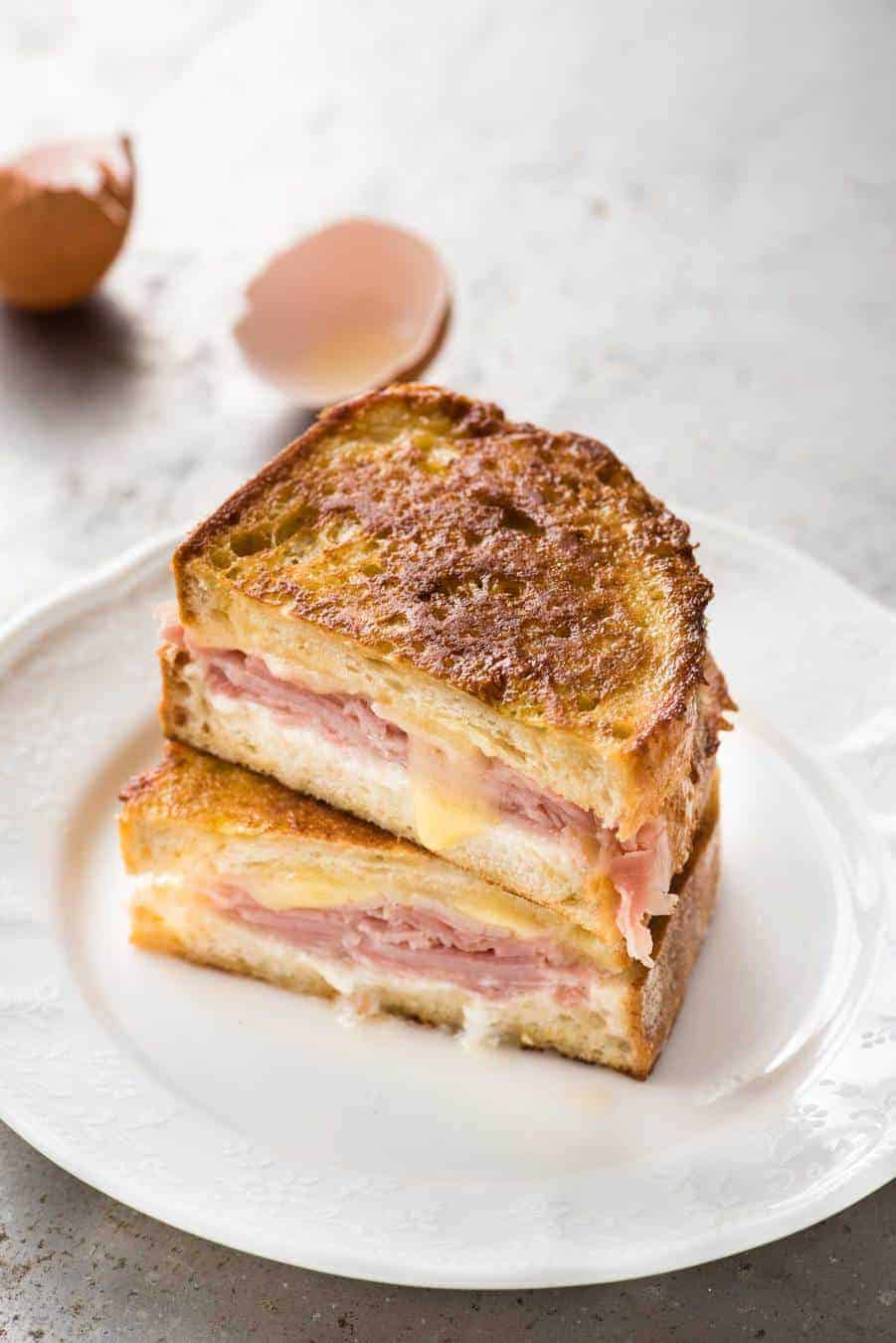 Monte Cristo Sandwich cut in half and stacked on each other on a small white plate, ready to be eaten.