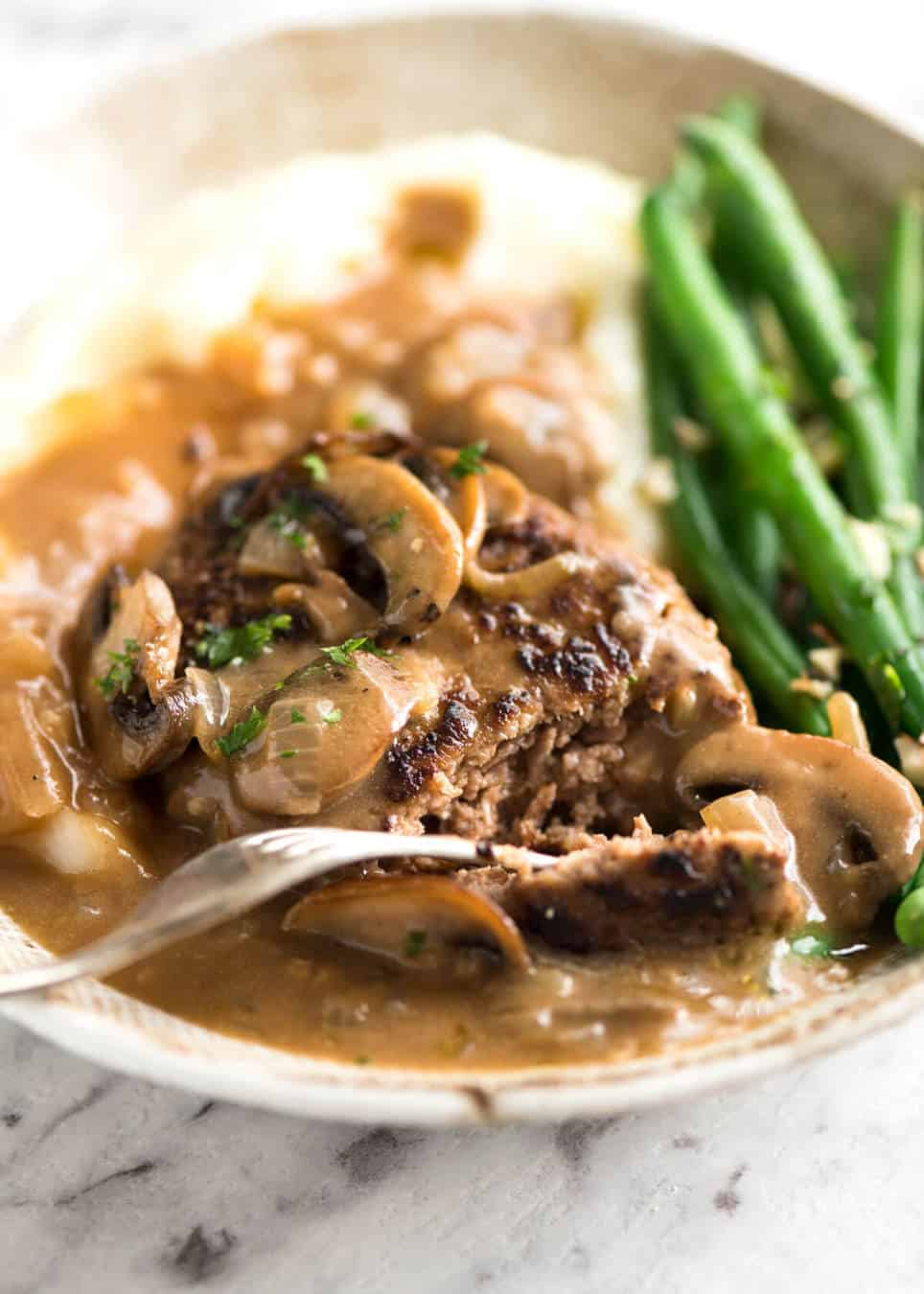 Close up of Salisbury Steak recipe on a plate with mashed potato and green beans.