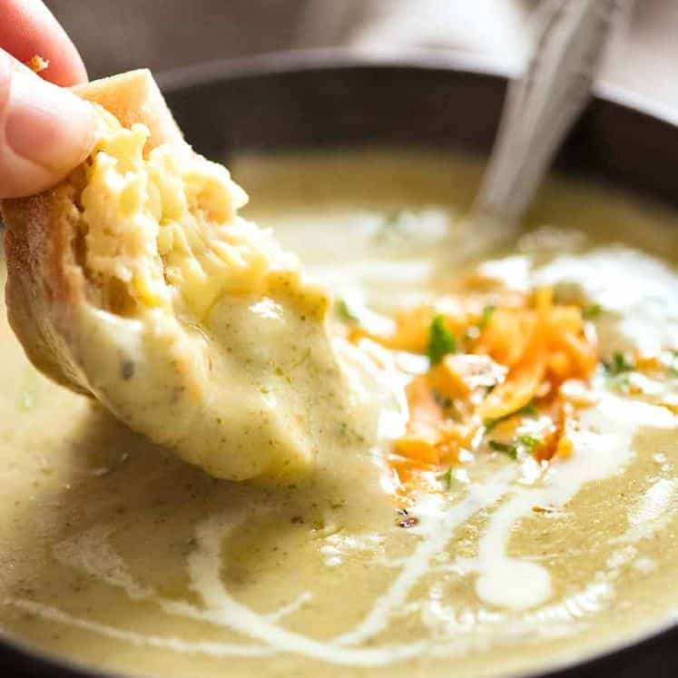 Warm crusty bread being dunked into creamy Easy Broccoli Soup