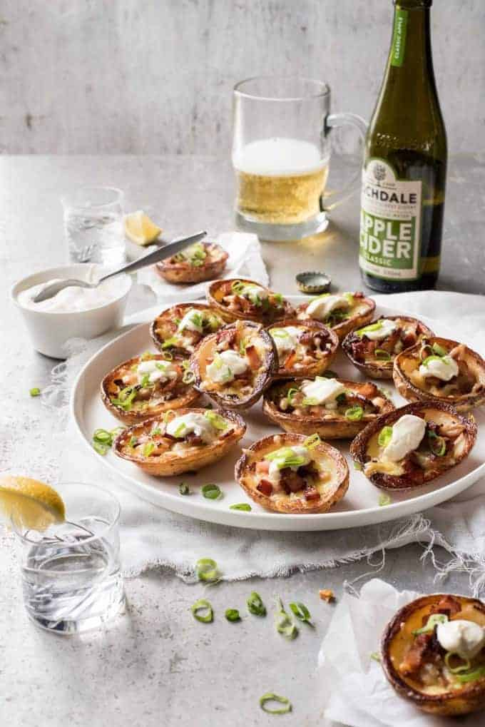 A platter of Cheese & Bacon Potato Skins with bottle and glass of cider