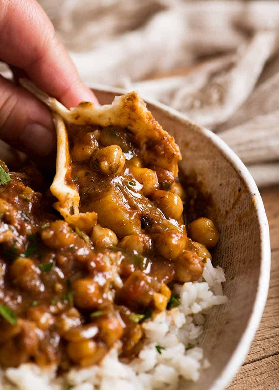 Close up of Chickpea Curry (Chana Aloo) being scooped up with Easy Soft Flatbread
